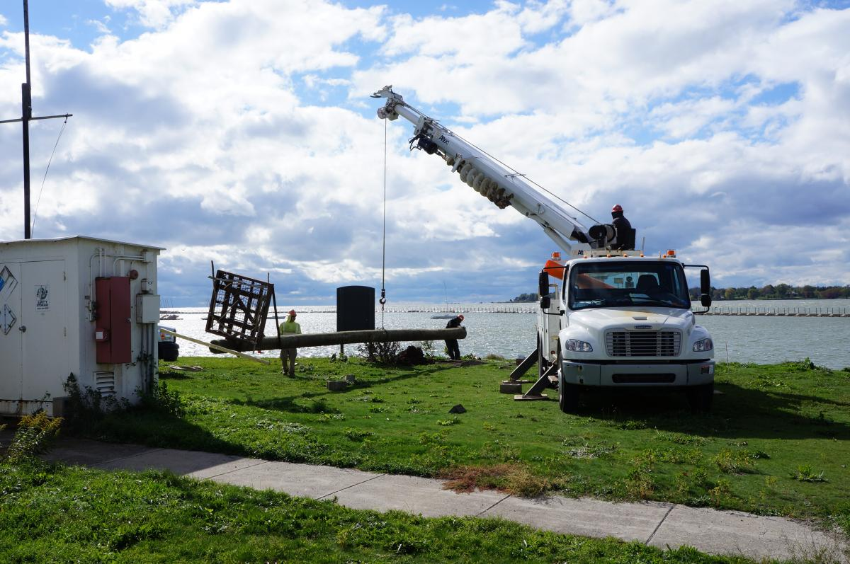 Workers use a truck with a crane to move the osprey pole near the waterfront. The pole is perpendicular to the ground and only a few feet above it, and two workers are guiding it along.