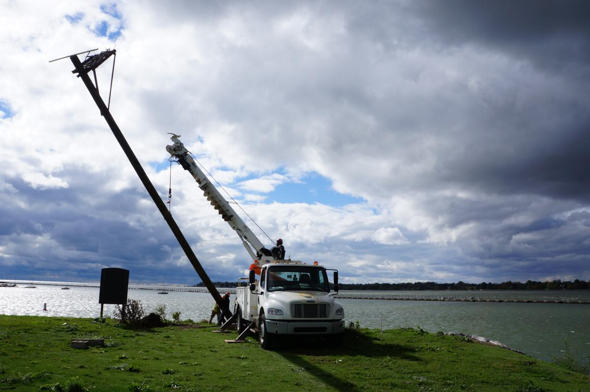 A truck with a crane holds up the osprey pole while two workers put its base in a hole.
