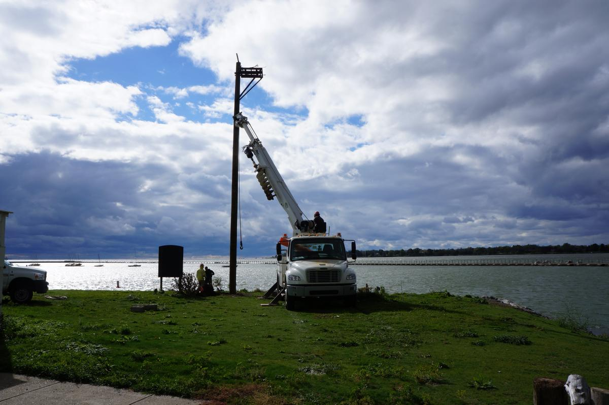 A truck with a crane holds the osprey pole upright in a hole by the waterfront.