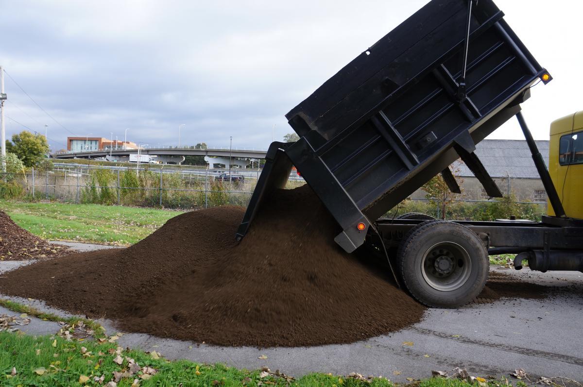 A dump truck pours a pile of dirt onto a roadway.