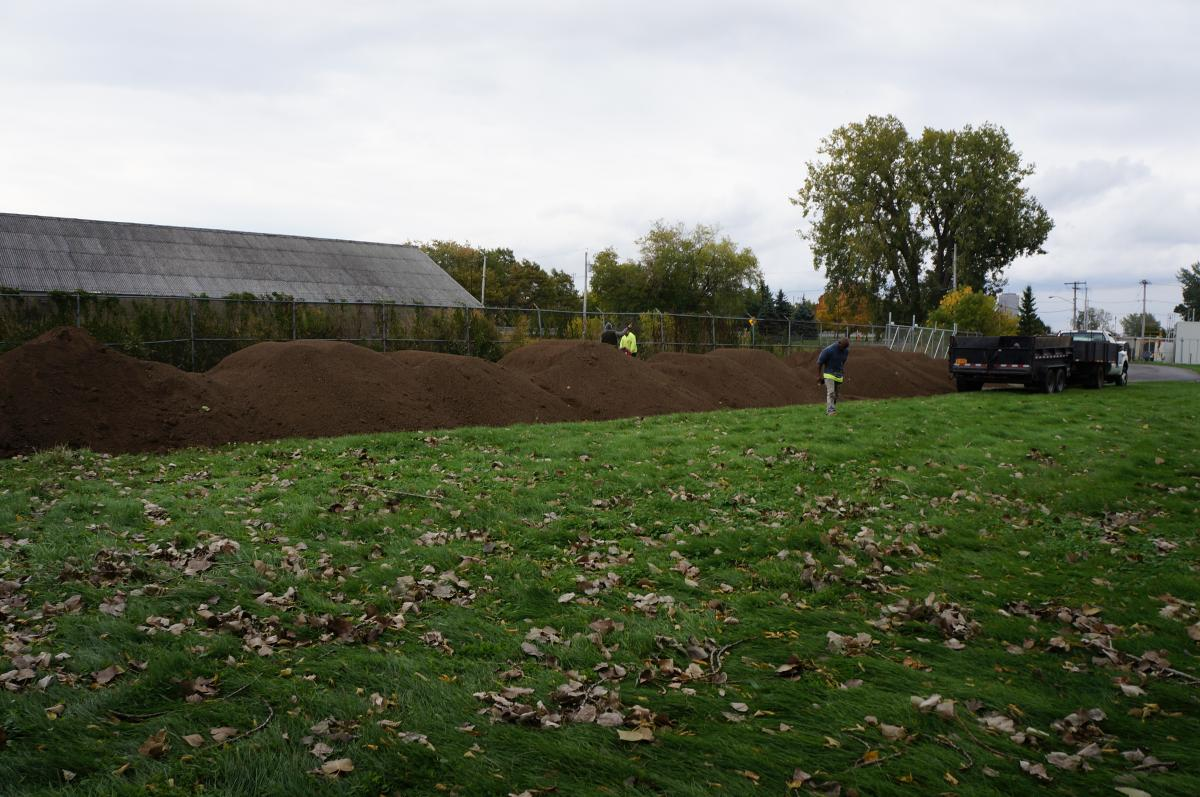 Landscapers work near a line of piles of top soil.