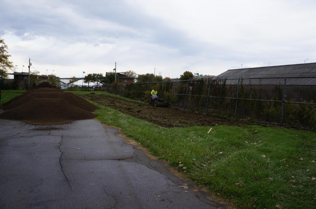 A person pushes a machine in a rectangular area along a fence to remove the grass. There are piles of dirt on a roadway nearby.