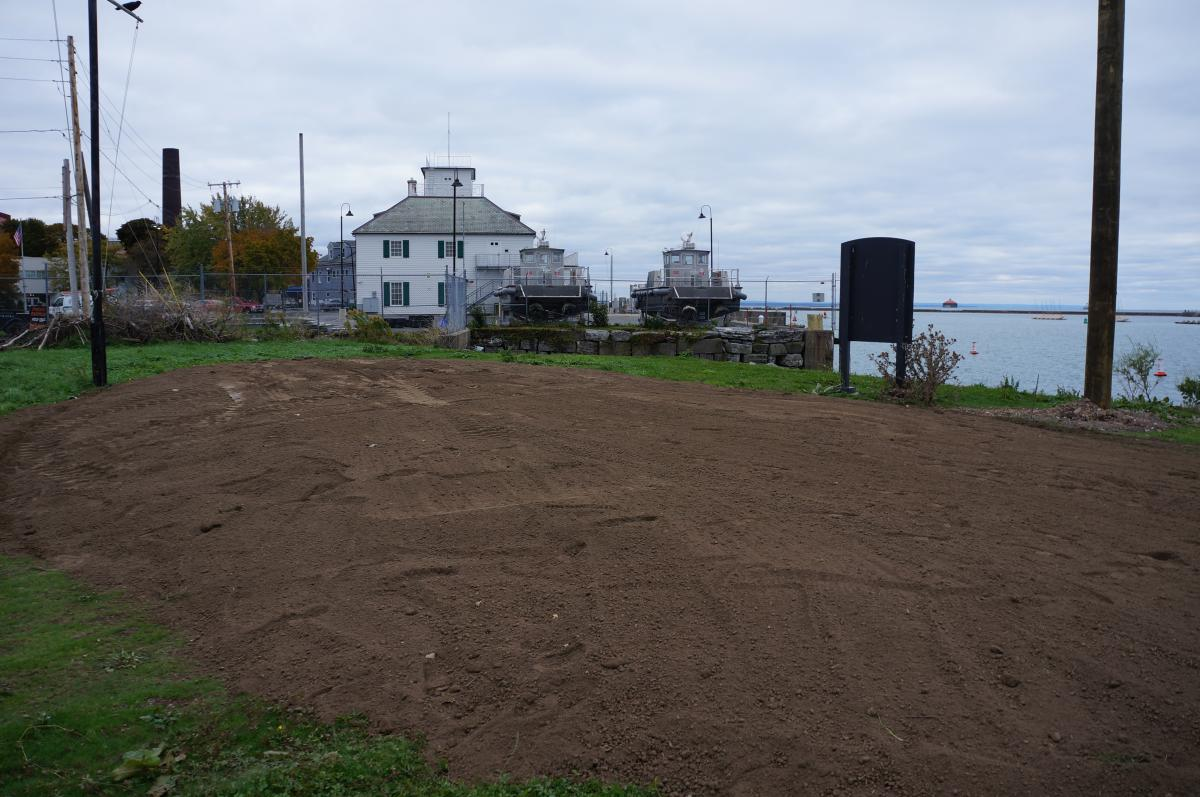 A large patch of dirt on the ground by the waterfront.