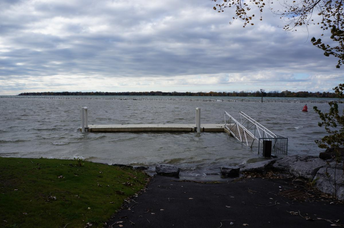 High water submerges a concrete dock but allows a metal ramp and floating dock to stay above water. The water level looks higher than normal since there is some water between the ramp and land.