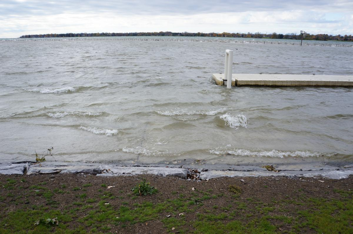 Water laps near the top of the stone barrier at the water's edge. A dock floats behind the water.