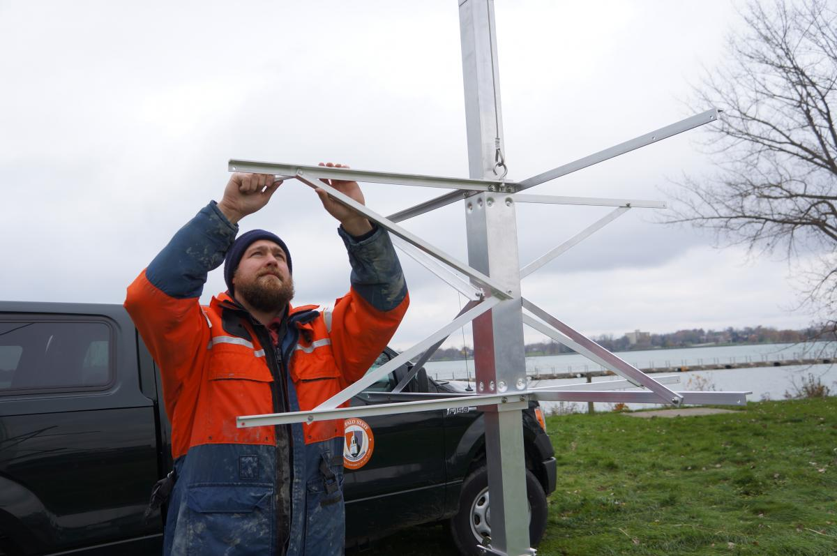 A person in a work suit and knit cap reaches over their head to assemble a metal frame on a pole. There is a vehicle behind them.
