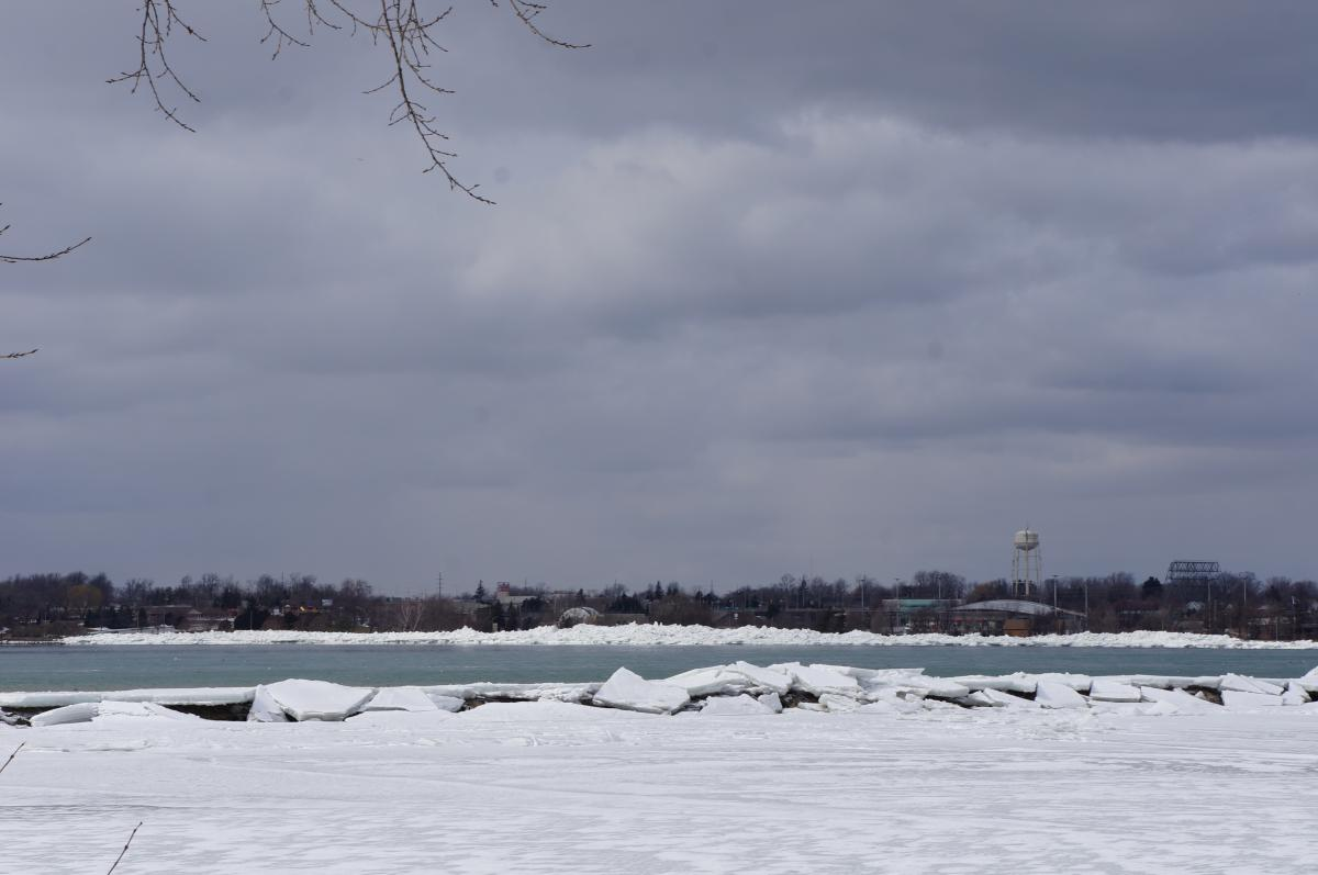 An ice-covered body of water next to an open area of water. There are large pieces of broken ice atop a breakwall between the two bodies of water. On the far shore, there is a giant pile of ice.