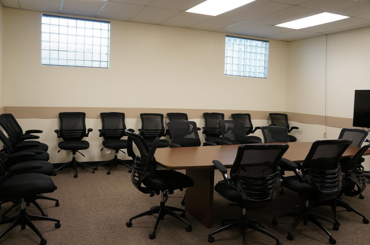 A conference room with computer chairs around a wooden table and along the walls.