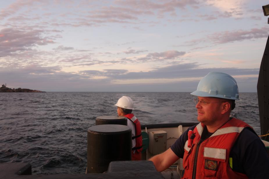 Two people wearing hard hats and life jackets stand at the edge of a boat.