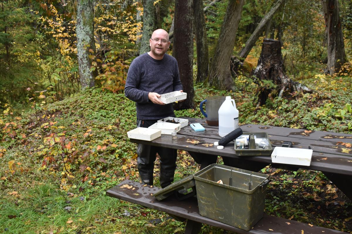A person stands by a picnic table in the woods in fall. There are plastic pans and jugs on the table, and a plastic pan in their hands.