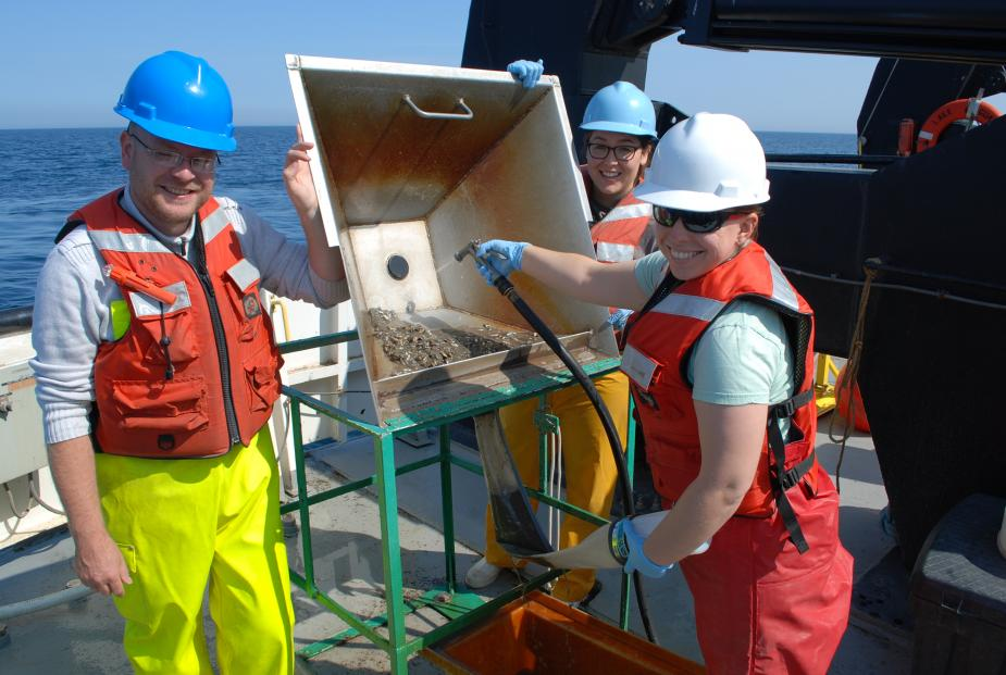 Two people tilt up a pan with sediment in it while a third person uses a hose to wash the sediment through a hole into a mesh sleeve with a bottle on the end of it. They are working on the deck of a large boat.