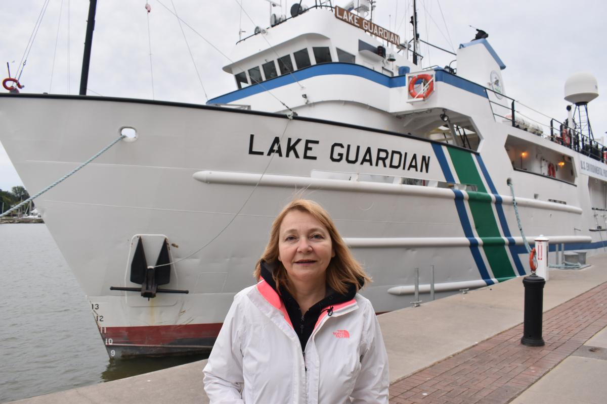 A person stands in front of a large docked boat labeled
