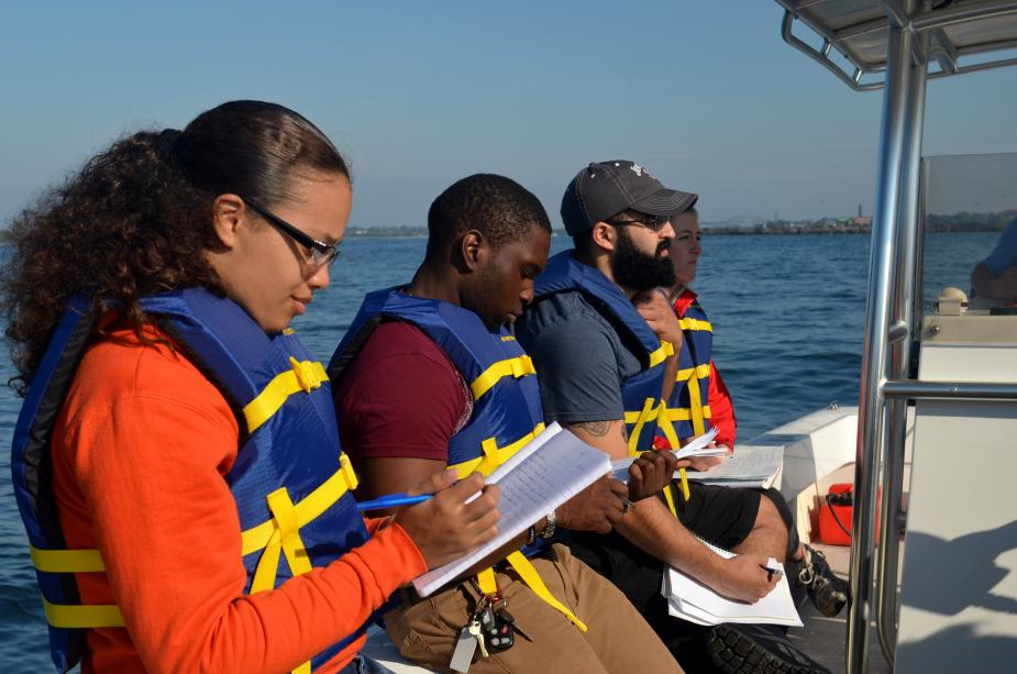 Students on a boat taking notes in a notebook