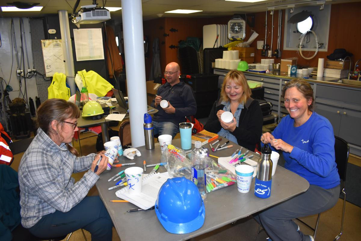 Four people sit in a lab. There are art supplies and they are drawing on styrofoam cups with markers. There is a hard hat on the table.
