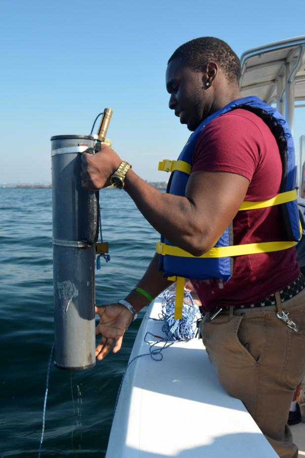 A student stands by the edge of the boat, holding a plastic cylinder over the water.