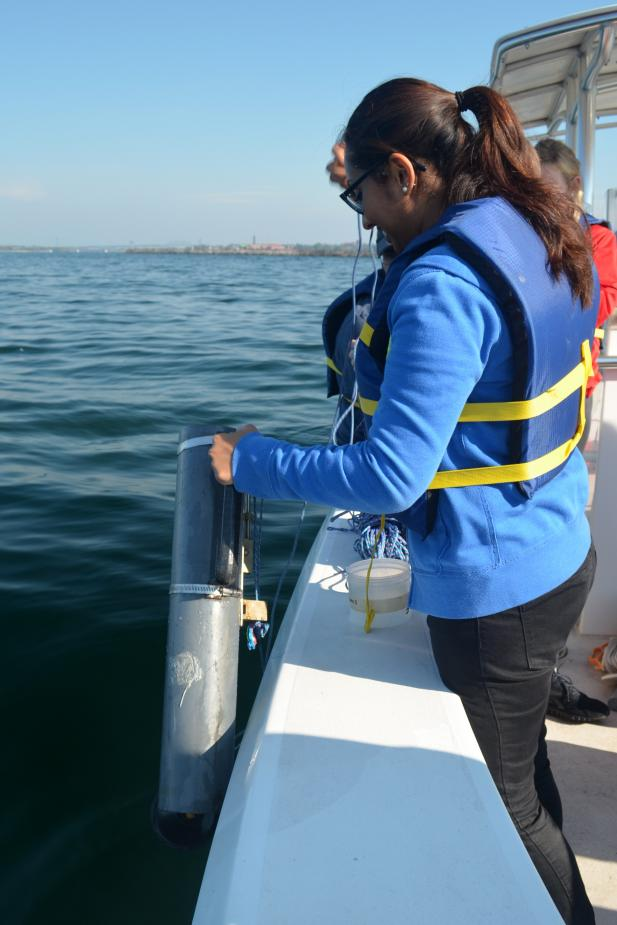 A different student stands by the edge of the boat, holding a plastic cylinder over the water.