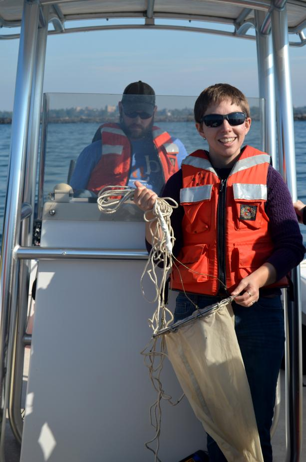 One person stands at the controls of a boat while another holds up a conical fabric net.