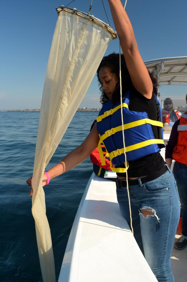 A student stands at the edge of a boat, pulling in a long fabric conical net.