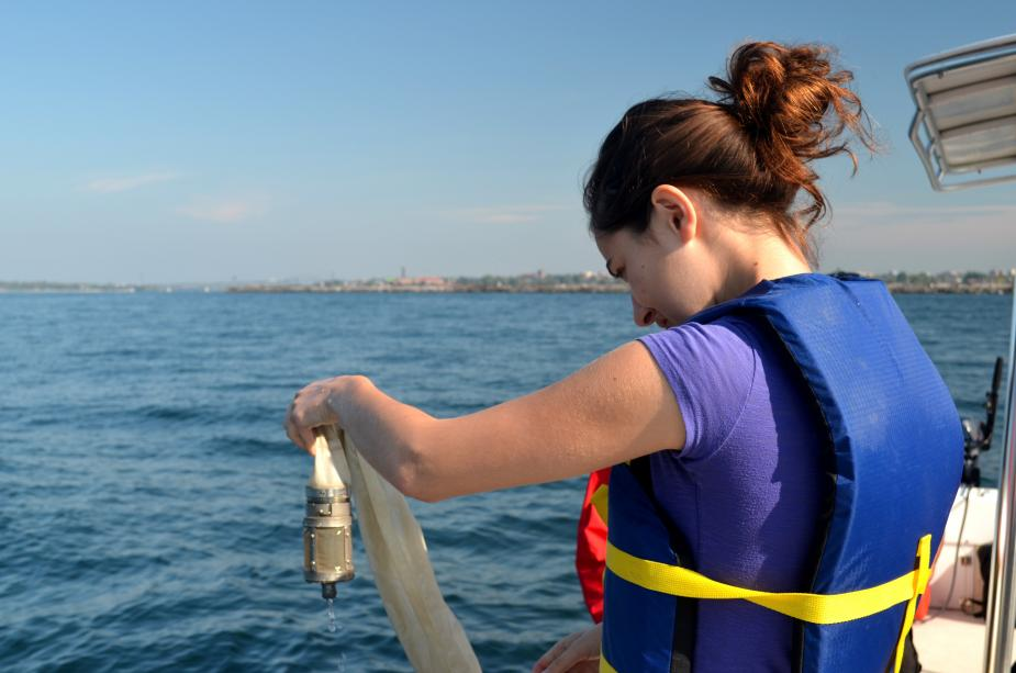 A student stands at the edge of a boat, holding up the little metal bucket at the end of a net.