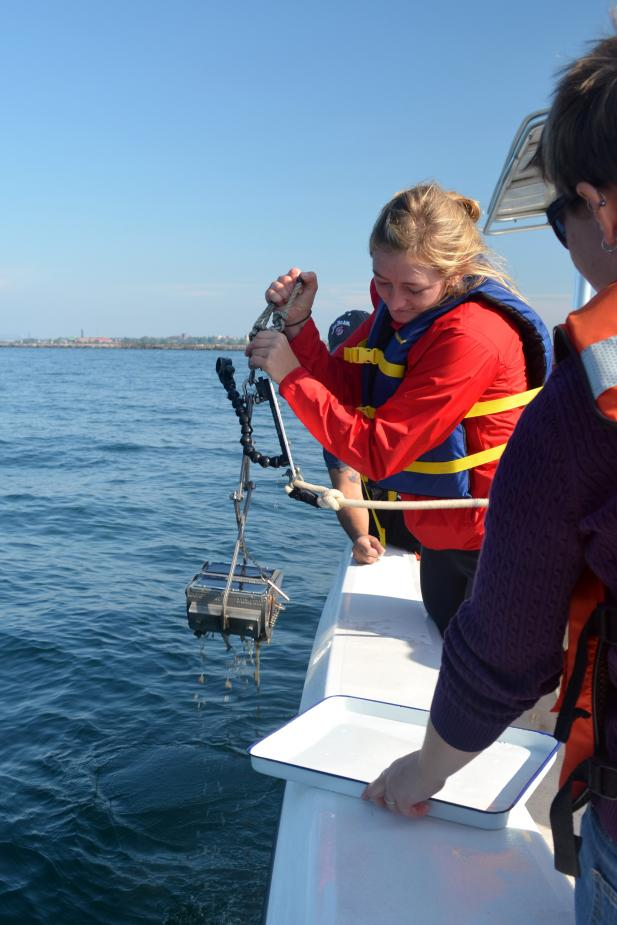 A student stands by the edge of the boat holding a metal grab contraption over the water