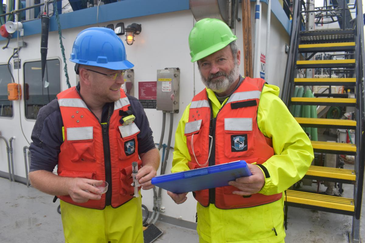 Two people wearing hard hats and life jackets stand on a large boat near a staircase. One is holding a clipboard and the other has a syringe.