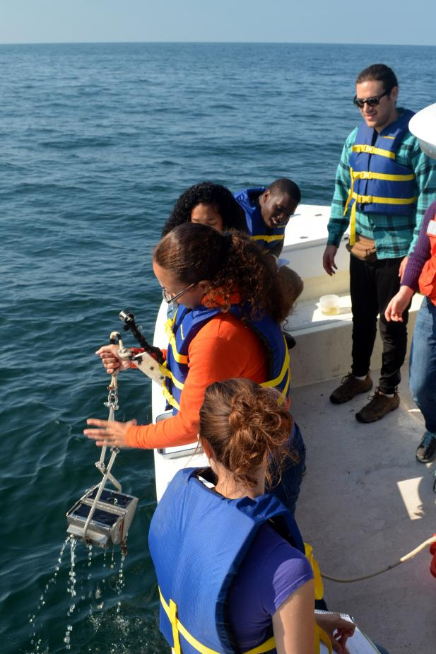 Other students look on as a different student stands by the edge of the boat holding a metal grab contraption over the water