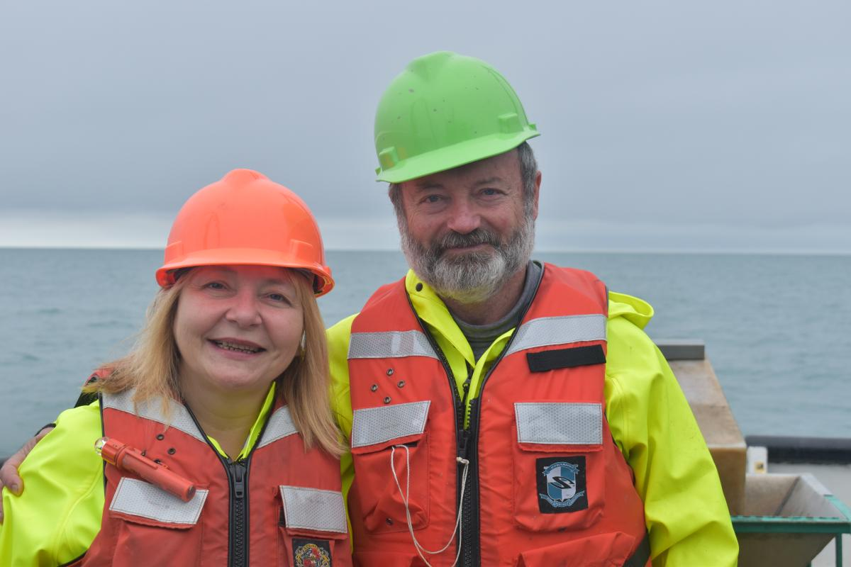 Two people pose for a picture while on the water. They are both wearing safety gear: hard hats, life jackets, and rain coats.