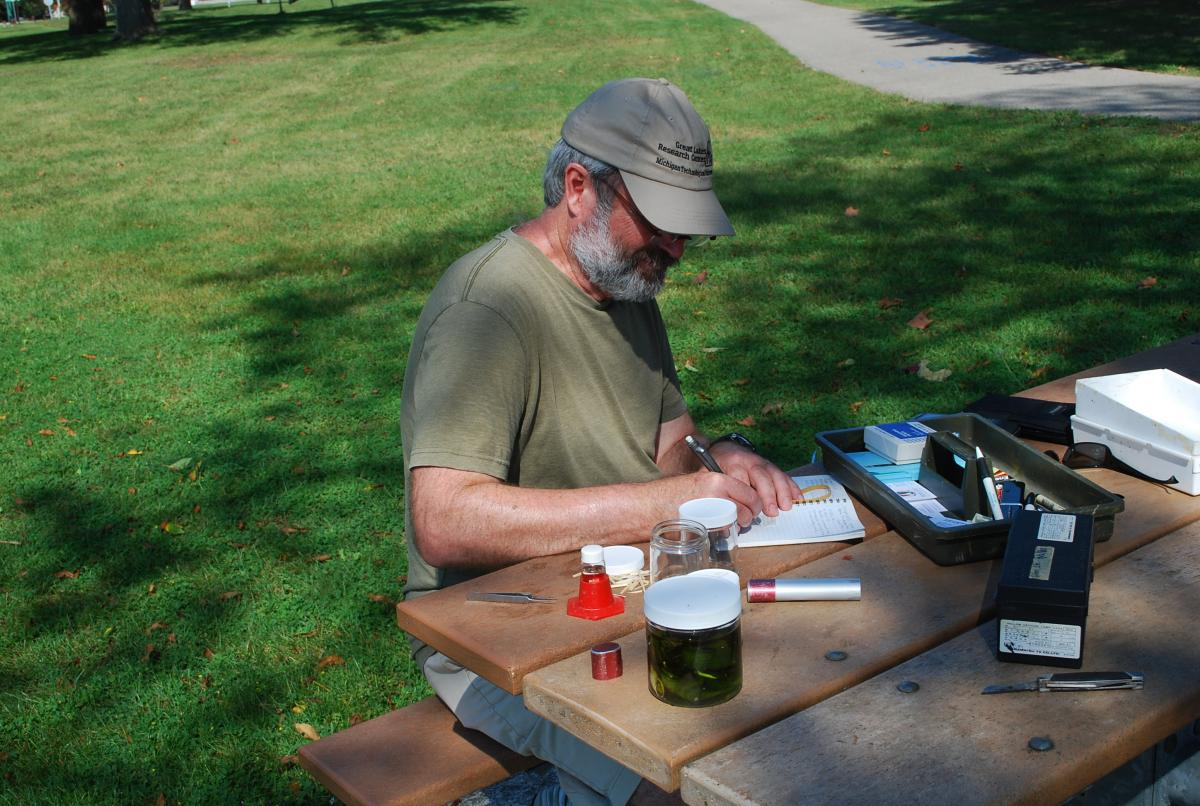 A person sitting at a picnic table with some jars and a toolbox. They are writing in a small notebook.