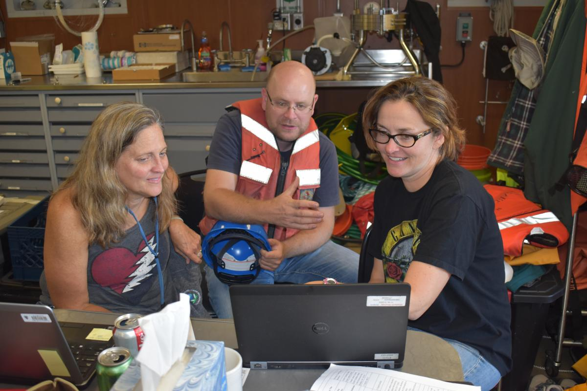 Three people sit in front of a laptop in a lab. One person is wearing a life jacket.