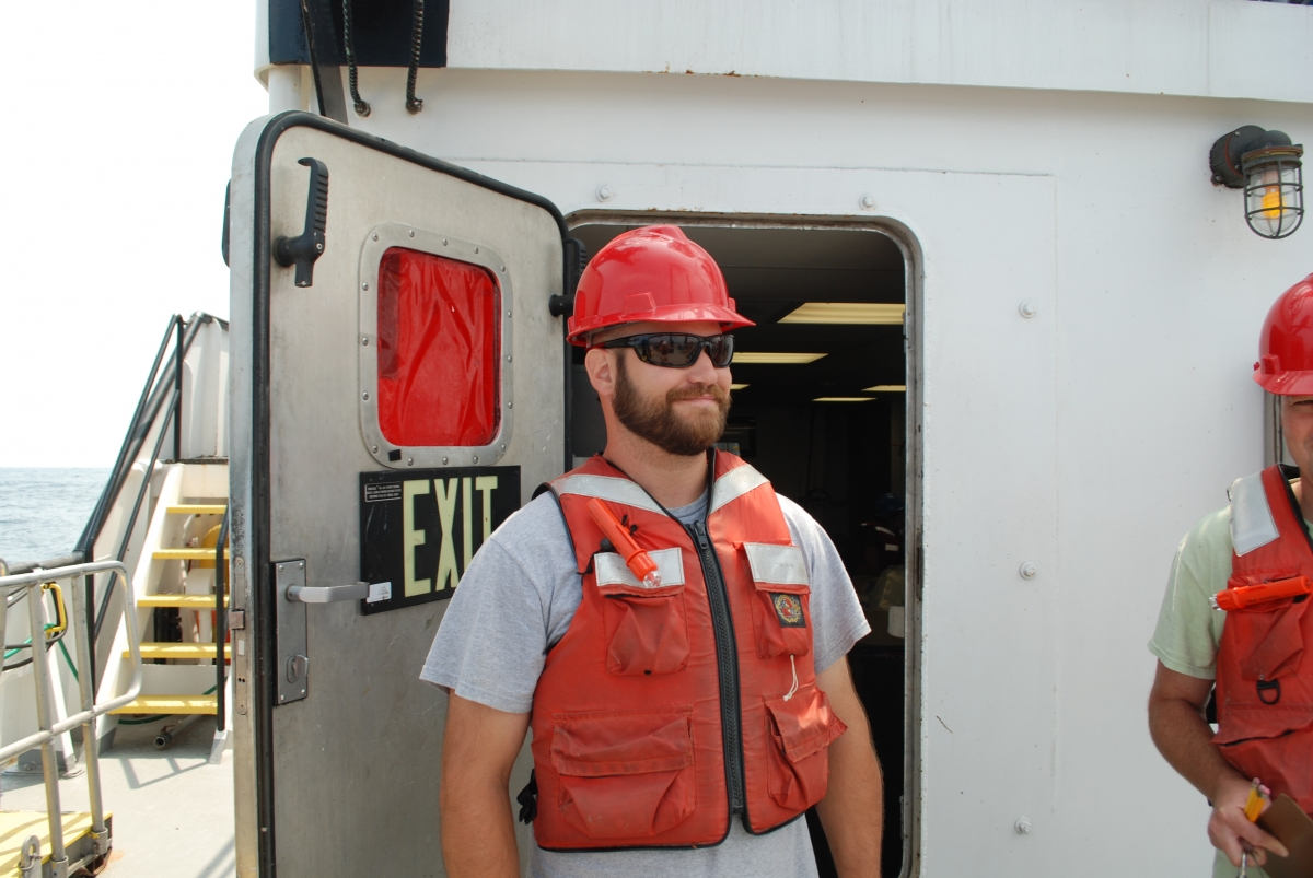 A person wearing a hard hat and life jacket stands by a bulkhead door labeled
