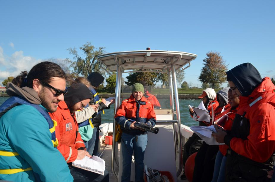 A person stands at the center of a boat holding up a cylindrical object while other people take notes.
