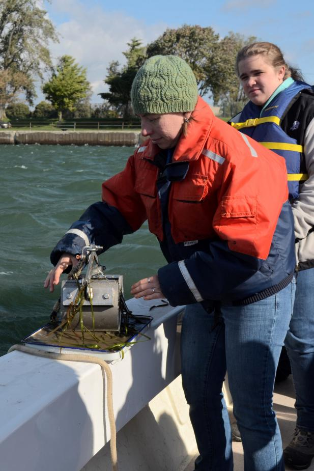 A person stands at the edge of a boat. They are opening a metal device that's on a pan, and there is mud and weeds coming out of the metal object.