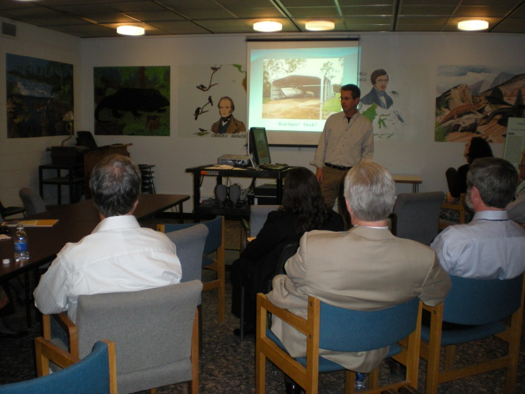 a group of people in chairs watch a presentation given by a different person at the front of the room. There is a presentation projected onto a screen, and murals painted on the walls of the room.