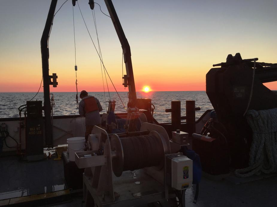A person working on the deck of a boat at sunrise or sunset
