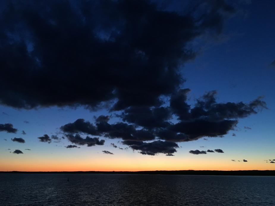 A dramatic image of a dark cloud in a dark blue sky over water, with an orange horizon