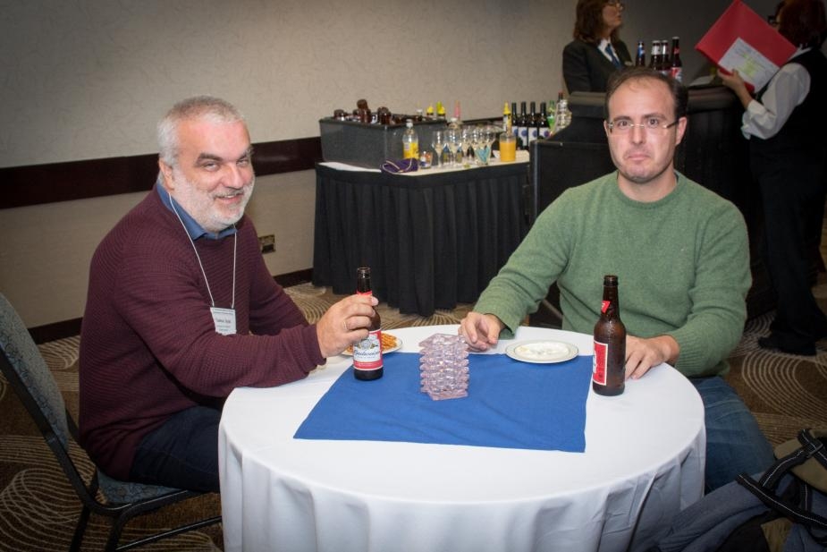 two people sitting at a table in a conference hall. There is a table with drinks behind them.
