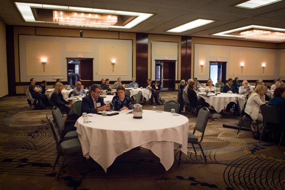people sitting at tables in a conference hall