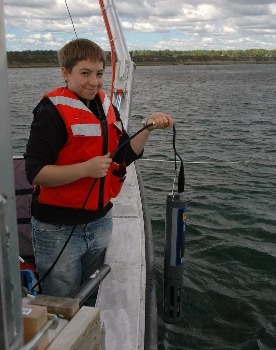 A person on a boat smiles as they lower a research instrument over the side of the boat
