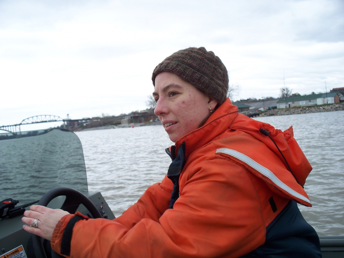 A person sitting at the helm of a boat, wearing a flotation suit and a knit cap