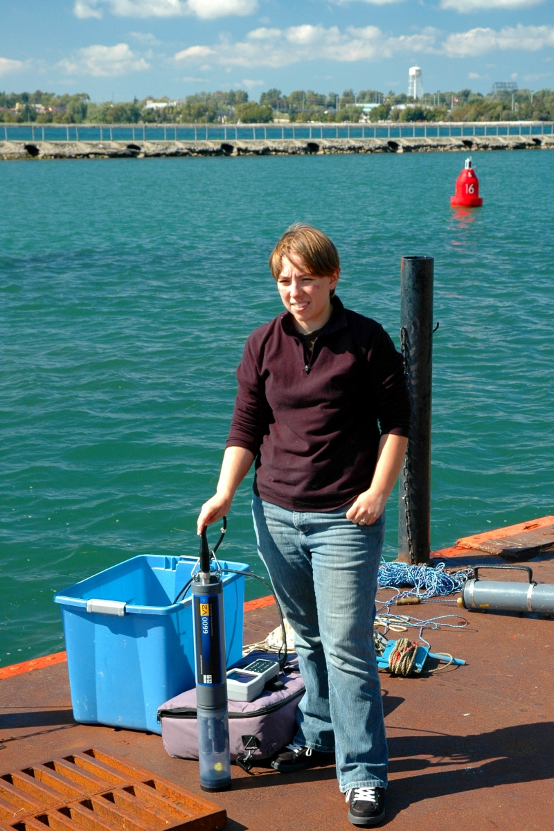 A person stands on a dock by the water with some research equipment