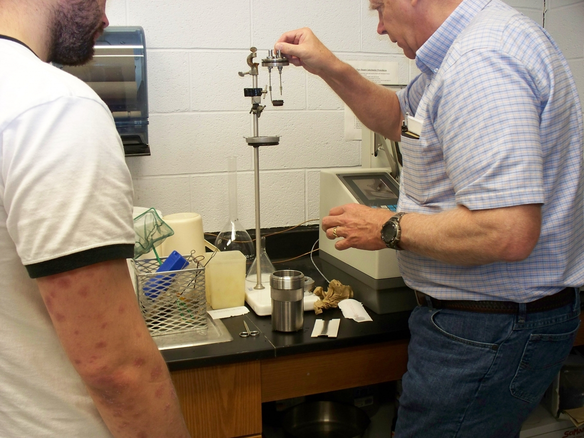 A person takes a metal lid with two rods and a tiny metal cup and prepares to set it on a stand. Nearby is a lab instrument and a large metal cup that the lid fits on. Someone watches.