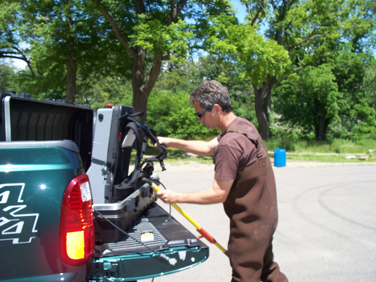 A person in chest waders takes a backpack unit out of a case on the tailgate. There is also a pole.