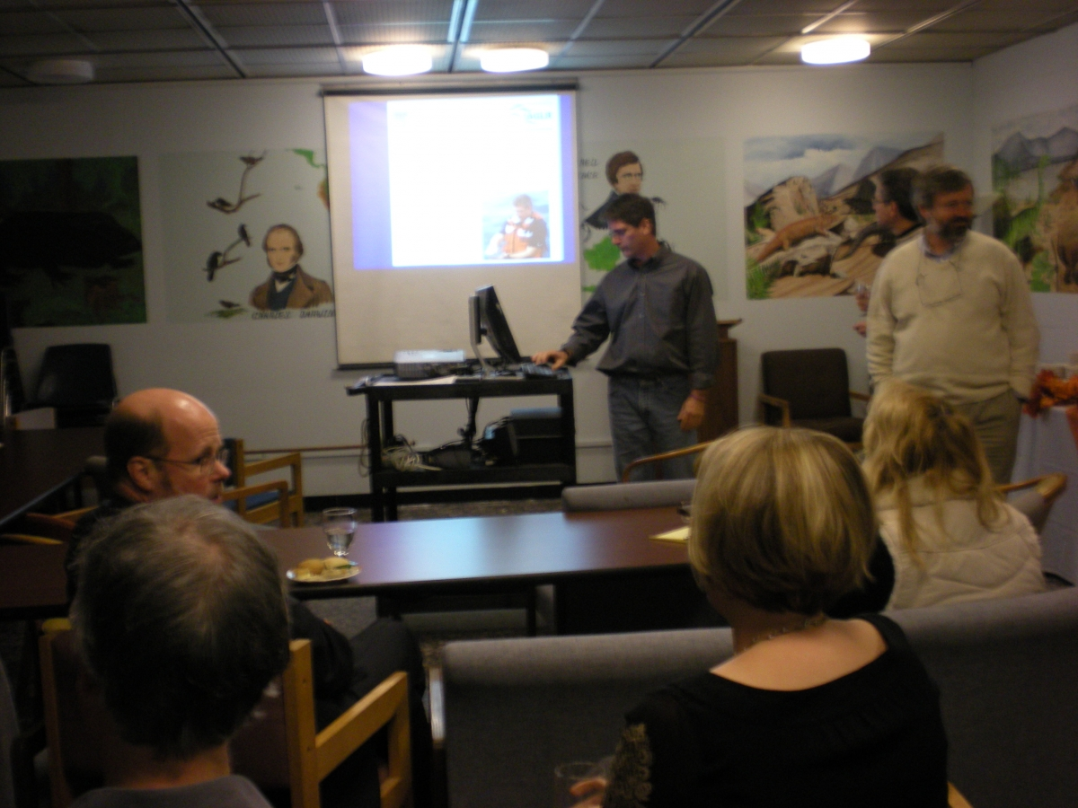 a group of people in chairs watch a presentation given by two people at the front of the room. There is a presentation projected onto a screen, and murals painted on the walls of the room.