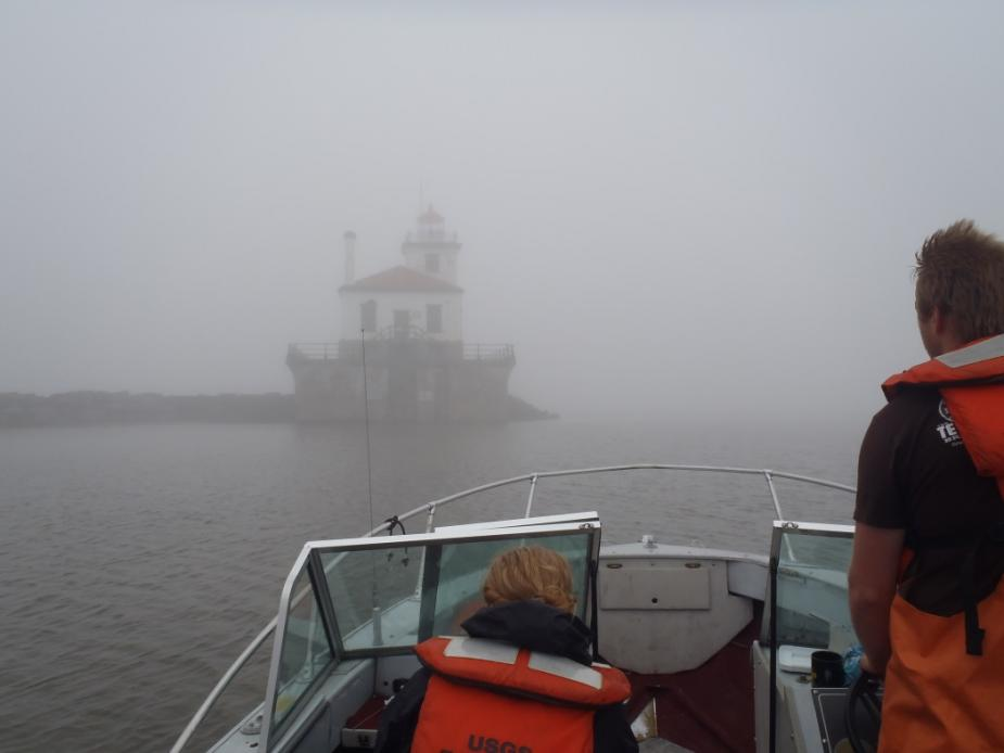 two people on a boat. It's foggy and one can barely see a lighthouse at the end of a breakwall near the boat.