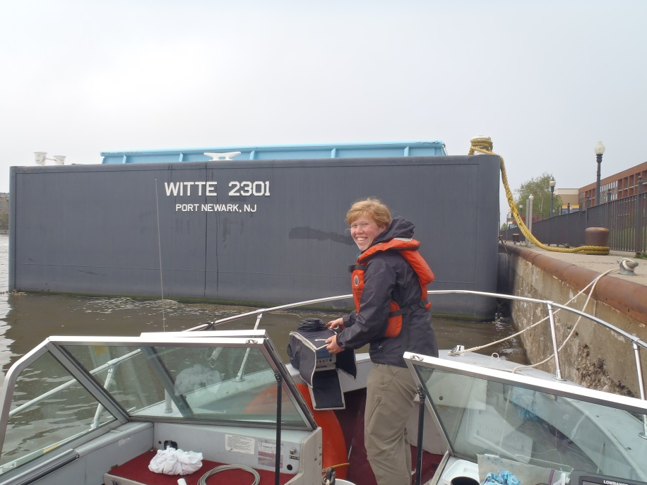 A person stands on a boat tied to a wall near a freight vessel. The back of the large boat is labeled