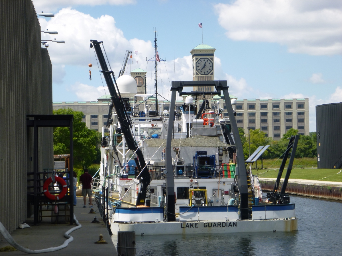 A large white boat tied up at dock by a building with a clock tower. The boat is labeled