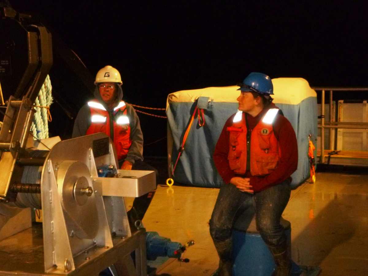 Two people in hard hats and life jackets sit on the back deck of a boat at night