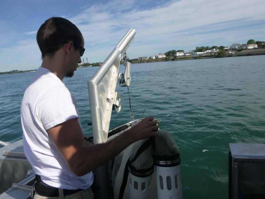 A person holds a net with two plastic buckets at the bottom, getting ready to put the net into the water.