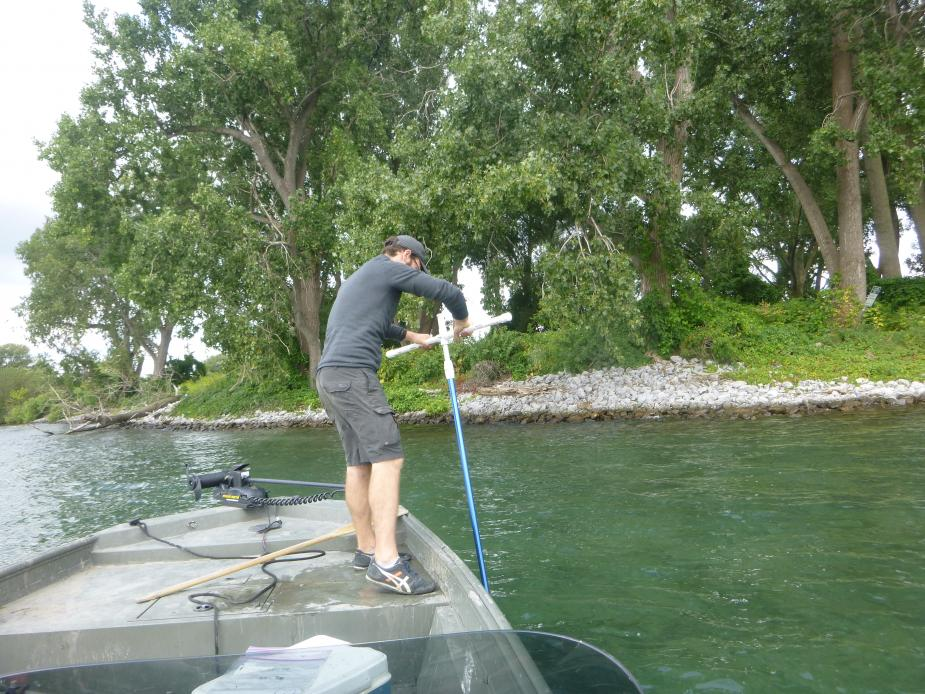 A person standing on the front of a boat. They are holding a long rod with a T on the end and using it in the water.