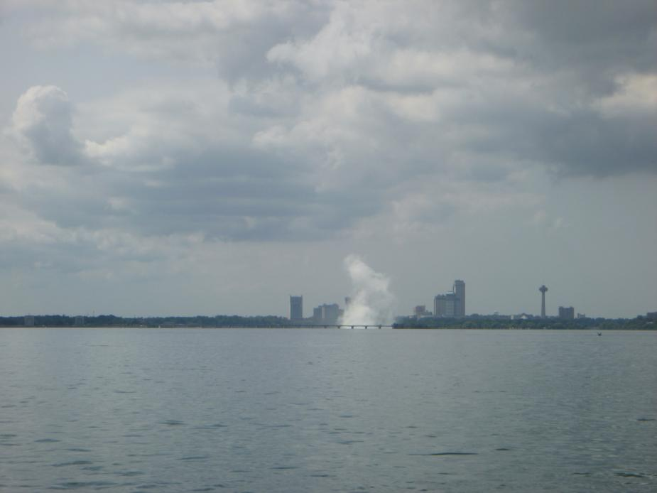 A plume of mist rises from the water in the distance.